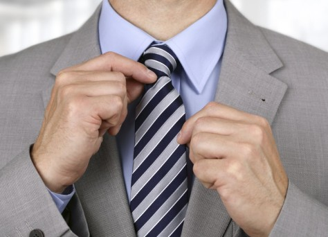 Businessman adjusting his necktie concept for anxiety, worried, meeting or ready for business