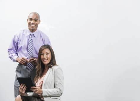 African American businessman (40s) with mixed race businesswoman (30s, Korean / Caucasian) in office board room.